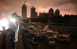 Des gens regardent des voitures empilées les unes sur les autres à l'entrée d'un tunnel à la suite des fortes pluies à Zhengzhou, dans la province chinoise du Henan, le 21 juillet 2021.