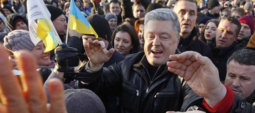 Petro Poroshenko salue les manifestants venus protester à Kiev la veille d'un sommet sur l'Ukraine, le 8 décembre 2019.