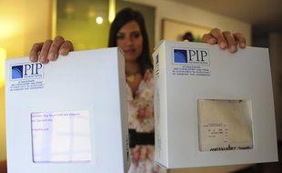 Une Vénézuélienne qui s'est fait poser des implants mammaires montre des boîtes de prothèses PIP, le 23 décembre 2011, à Caracas (Vénézuela).
