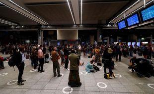 Des voyageurs patientent devant les écrans d'affichage en gare Montparnasse - photo d'illustration