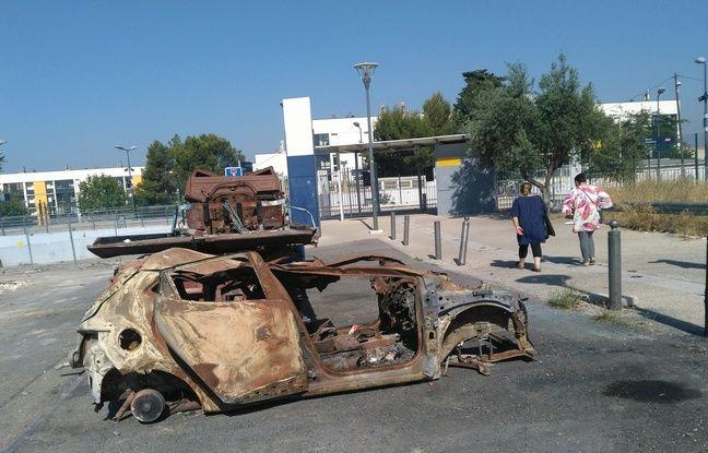 Des passants à côté d'une carcasse de voiture, à la Busserine à Marseille.