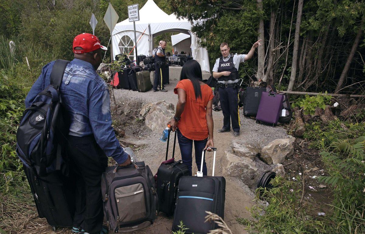 Un officier de la police canadienne fait face à un couple de migrants en provenance des Etats-Unis. Un point de passage temporaire a dû être aménagé près de Saint-Bernard-de-Lacolle (Québec).  – Charles Krupa/AP/SIPA