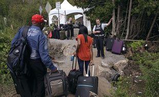 Un officier de la police canadienne fait face à un couple de migrants en provenance des Etats-Unis. Un point de passage temporaire a dû être aménagé près de Saint-Bernard-de-Lacolle (Québec).