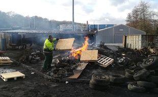 Un salarié de l'entreprise Arjowiggins alimente un feu devant l'établissement