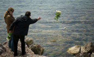 Un homme jette des fleurs à la mer lors d'un hommage pour Florence Arthaud, le 26 avril 2015 sur l'île Saint-Honorat
