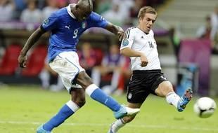Mario Balotelli, ici à la lutte avec Philipp Lahm, frappe fort. Il inscrit ici le deuxième but italien contre l'Allemagne, en demi-finale de l'Euro (jeudi 28 juin 2012)