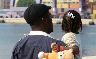 Un migrant et sa fille dans le port de Palerme, le 11 juillet 2015