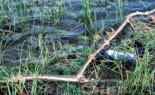 Une bouteille en plastique dans une rivière.