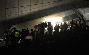 Les secours tentent de désincercérer les passagers toujours coincés dans le train accidenté, en Espagne, le 24 juillet 2013.