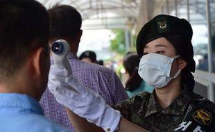 Une soldate prend la température de visiteurs à l'entrée du ministère de la Défense, le 9 juin 2015 à Séoul