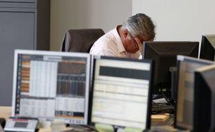 Un homme se prend la tête dans les mains devant son ordinateur