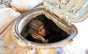 Une militaire syrienne conduit un char à Damas le 25 mars 2015