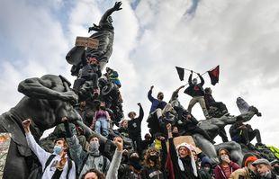Jeunes manifestants sur la statue du Triomphe de la République de Dalou, place de la Nation, à Paris, le 1er mai 2021.