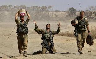Des soldats israéliens rentrent à leur camp de base le long de la frontière avec Gaza, après avoir combattu dans l'enclave palestinienne, le 4 août 2014