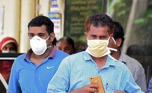 En Inde, deux hommes se protègent d'un virus mortel à Kozhikode le 21 mai 2018.