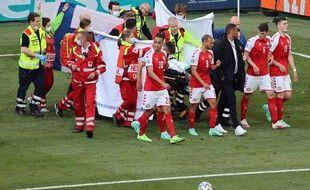 Les joueurs danois et les secouristes raccompagnent Christian Eriksen, victime d'un malaise en plein match samedi.