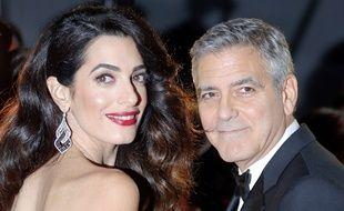 Photo d'archives du 24 février 2017, montrant l'acteur George Clooney et son épouse, l'avocate Amal Clooney, à leur arrivée à la 42e cérémonie des César, à Paris.