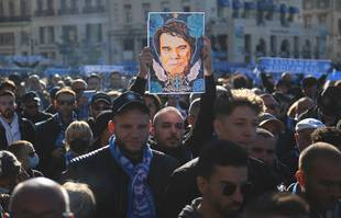 Un homme brandit un portrait de Bernard Tapie avant une messe organisée pour ses funérailles à la cathédrale Major de Marseille, le 8 octobre 2021.