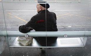 Une personne âgée, de dos, attentent le bus. Illustration sur la vieillesse.