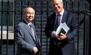 Masayoshi Son, PDG de SoftBank, et Stuart Chambers, président de ARM Holdings, photographiés devant le 11 Downing Street à Londres, le 18 juillet 2016, après avoir rencontré le ministre britannique des Finances