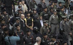 Un suspect (centre) dans l'attentat à la bombe de Bangkok est escorté par la police lors de la reconstitution des faits dans le centre de la capitale thaïlandaise, le 9 septembre 2015