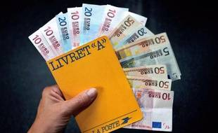 A person holds a Livret A saving book and banknotes on July 19, 2012 in Lille. AFP PHOTO / PHILIPPE HUGUEN