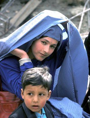 """'""""Eyewitnessed"""", une femme afghane lève son voile en amenant son fils à l'école, à Kaboul, pour la première fois après la chute des talibans en 2002."""