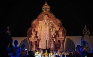 Portrait géant du roi Bhumibol Adulyadej devant le Grand Palais à Bangkok lors du 87 anniversaire du monarque, le 5 décembre 2014. Parmi les hauts dignitaires soutenant des bougies au premier plan, le premier ministre Chan-O-Cha (à g)