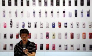 Un homme se servant de son téléphone portable lors d'une exposition sur les mobiles, à Tokyo, le 23 mai 2010