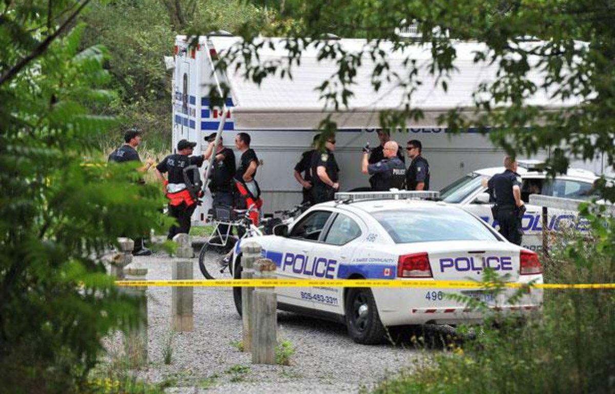 Des enquêteurs près de l'endroit où a été retrouvé la tête d'une femme, le 16 août 2012, à Mississauga (Canada). – A.V.ELKAIM / AP / SIPA