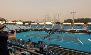 Un court de tennis du Melbourne Park où se déroule l'Open d'Australie, le 15 janvier 2020, avec les grattes-ciel de Melbourne couverts par le smog de la fumée des incendies.