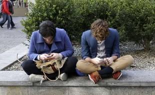 Illustration: De jeunes gens utilisent leur smartphone.