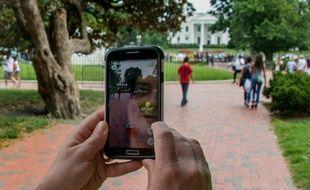 Une femme se promène dans la rue en jouant au Pokemon Go sur son téléphone, le 21 juillet 2016 à Washington