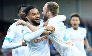Marseille's French forward Valere Germain (R) congratulates his teammates after scoring during the French L1 football match Guingamp vs Olympique of Marseille (OM) on May 11, 2018 at the Roudourou Stadium in Guingamp, western France. / AFP PHOTO / Fred TANNEAU