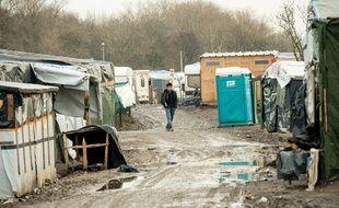 """Un homme marche dans la """"jungle"""" de Calais, le 25 février 2016."""