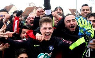 Le portier de l'Olympique Strasbourg entouré d'autres joueurs et du public du club du quartier de Cronenbourg en périphérie de la capitale alsacienne.