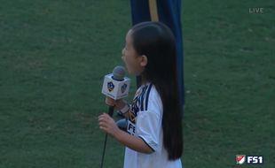 Une jeune fille chante l'hymne américain.