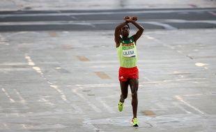 L'Ethiopien Feyisa Lilesa franchit la ligne d'arrivée du marathon des JO de Rio avec les bras croisés au-dessus de sa tête en signe de protestation contre son gouvernement, le 21 août 2016.