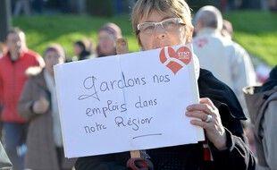Illustration d'une femme brandissant une pancarte lors d'une manifestation en faveur du maintien du Crédit Mutuel Arkea en 2016 à Brest.