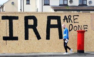 Un homme marche devant un graffiti «C'en est fini de l'IRA» à Londonderry, le 20 avril 2019.