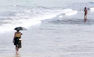 Une femme marche avec une ombrelle pour se protéger du soleil sur la plage de Dinard (Ille-et-Vilaine)