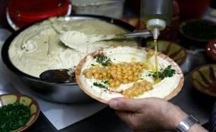 Un restaurateur palestinien prépare un plat de hoummous, purée froide à base de pois chiches, dans la vieille ville de Jérusalem, le 12 septembre 2015