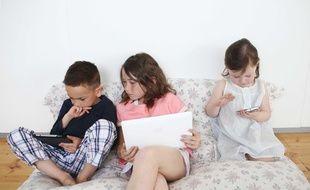 Trois enfants utilisent différents appareils électroniques dans le salon;