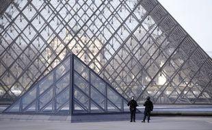 Des policiers patrouillent devant la pyramide du Louvre après l'attaque de militaires.
