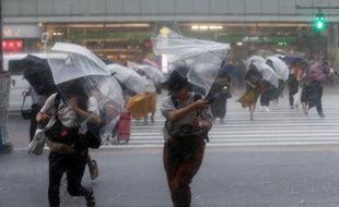 A Tokyo, des passants se protègent des pluies torrentielles du typhon Jongdari, le 28 juillet dernier.