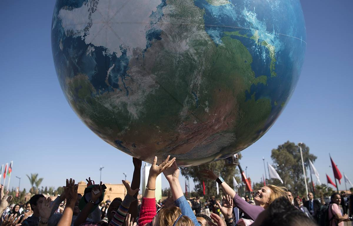 Des membres des délégations internationales jouent avec un globe géant, lors de la conférence de la COP22, le 18 novembre 2017 à Marrakech, au Maroc.   – FADEL SENNA / AFP