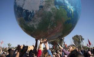 Des membres des délégations internationales jouent avec un globe géant, lors de la conférence de la COP22, le 18 novembre 2017 à Marrakech, au Maroc.