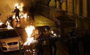 Des policiers touchés par des cocktails molotov tentent d'éteindre les flammes, lors d'affrontements avec des manifestants à Corte, en Corse, le 16 février 2016