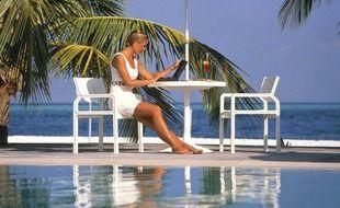 Une femme au bord de la piscine avec son ordinateur portable
