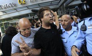 Des officiers de police israéliens emmènent un activiste pro-palestinien lors d'une manifestation à l'aéroport Ben Gourion, à Tel Aviv, le 8 juillet 2011.